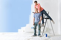 Smiling woman on ladder leaning on man next to painted wall