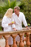 Couple in bathrobes standing at railing and holding apple