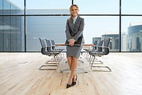 Confident businesswoman holding laptop in conference room