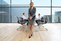 Pensive businesswoman holding laptop in conference room