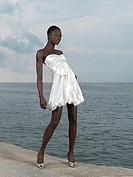 Beautiful woman in white dress posing on a sea shore