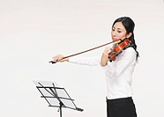 Young woman playing violin with music stand