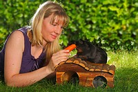 Woman feeding Guinea Pig with carrot