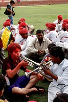 India, Rajasthan State, during the festival of colours, Indians showing a Japanese man how to play the trumpet