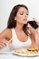 Woman drinking a cola with hamburger and fries