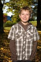 Portrait of a boy amidst autumn leaves Sweden.
