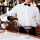 Waiter pouring wine into a glass