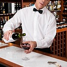 Waiter pouring red wine into a wine glass in a bar