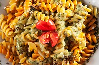 Close_up of a bowl of rotini topped with pesto sauce