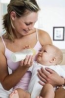 Young mother feeding baby 6_12 months on bed