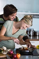Young couple in kitchen, cooking together, making pasta sauce, hugging, smiling