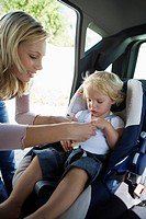 Young mother securing baby 12_24 months in car seat