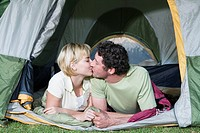 Young couple in tent, camping, kissing