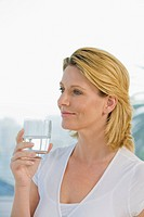Mature woman holding glass of water