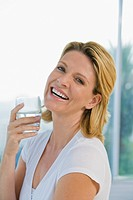 Mature woman laughing and holding glass of water
