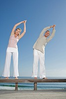 Mature couple standing on wooden bench outdoors doing yoga exercises