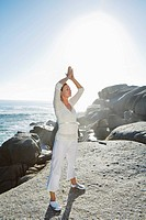 Mature woman standing on cliff with arms raised doing Yoga exercises