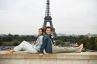 Young couple lying back to back on wall, Eiffel tower in background