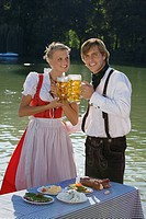 Young couple in traditional Bavarian outfit, having meal in beer garden Munich