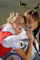 Young couple in traditional Bavarian outfit, sharing meal in beer garden, Munich