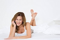 Women on bed using cell phone
