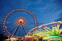 Illuminated fairground rides at night, Oktoberfest, Munich, Germany