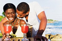 African couple drinking cocktails on patio overlooking ocean