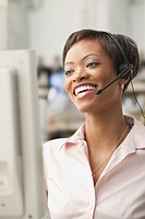 African woman wearing headset at computer
