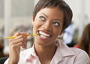 African woman biting eraser of pencil and looking up