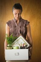 Dejected businesswoman holding box of office belongings