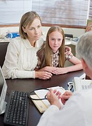 Doctor talking with mother and daughter in office
