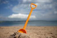 childs toy plastic spade stuck into the sand on a beach in the uk