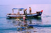 Vietnam, Phu Quoc island Southwest, fishermen removing fishing nets in Bai Truong