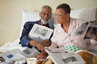 African couple drinking coffee and reading newspaper in bed