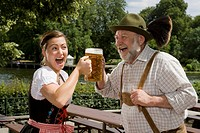 A traditionally clothed German man and woman in a beer garden toasting glasses