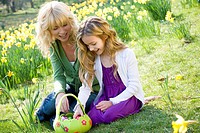 Mother and daughter looking at a basket full of Easter eggs