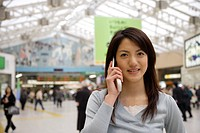 Portrait of a young woman using mobile phone at the station