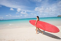 A woman walking on beach with surfboard in hand