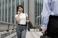A professional woman converses on the mobile phone as she moves