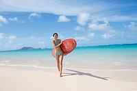 A young woman holding surfboard at beach