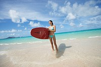 A young woman holding surfboard on beach