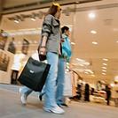 Two women walking with shopping bags outside a shop.