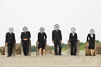 Group of businesspeople leaning on wood with bull´s eye on face