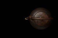 Iron kettle against black background, directly above