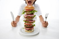 Boy 10_11 holding fork and knife with multi_layered sandwich, mid section