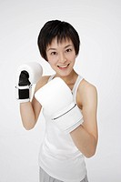 Young woman wearing boxing gloves, smiling, portrait