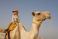 Child, girl, 5, riding a camel in the Marsa Alam desert, Red Sea, Egypt