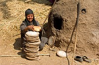 Woman making bread in mud oven, with flat stones used to put dough on, to rise in sun before baking, West Bank, Luxor, Egypt