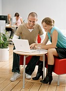 Man and woman sitting at coffee table and using laptop