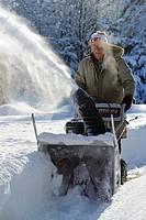 Man operating gasoline powered snow blower
